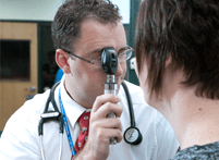 Image of ATSU student performing an eye inspection on a patient