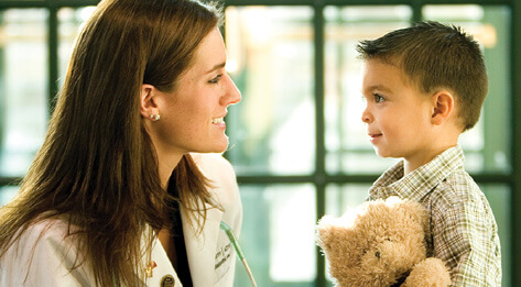 A young woman wearing a white lab coat, talking with a small boy holding a teddy bear.