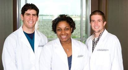 Three medical students wearing white lab coats smiling, posed for a picture.