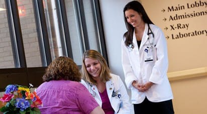 Female medical students wearing white lab coats, smiling while consulting with a patient.