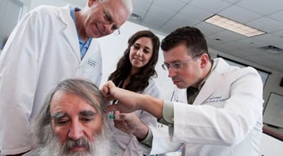 Image of ATSU audiology professor demonstrating proper patient ear exam to ATSU audiology students
