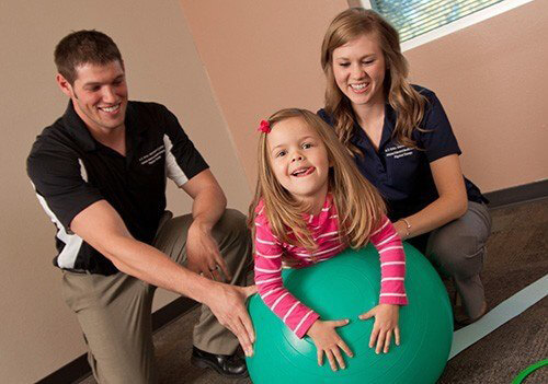 Two ATSU students with a child patient on an exercise ball