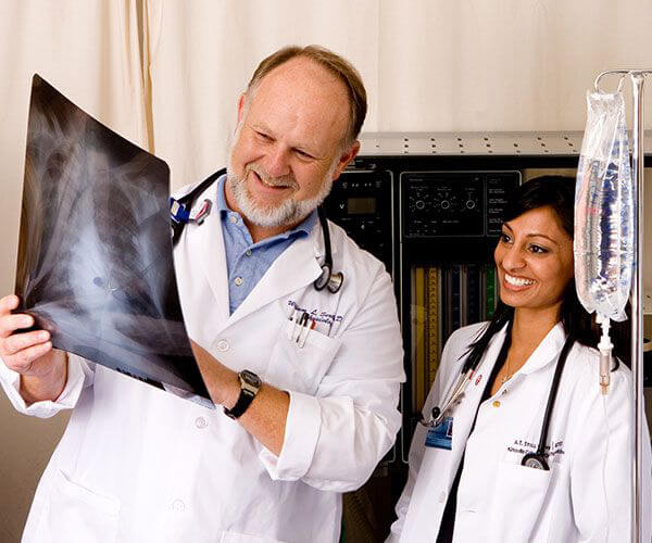 Male and female doctors wearing white lab coats and examining an x-ray.