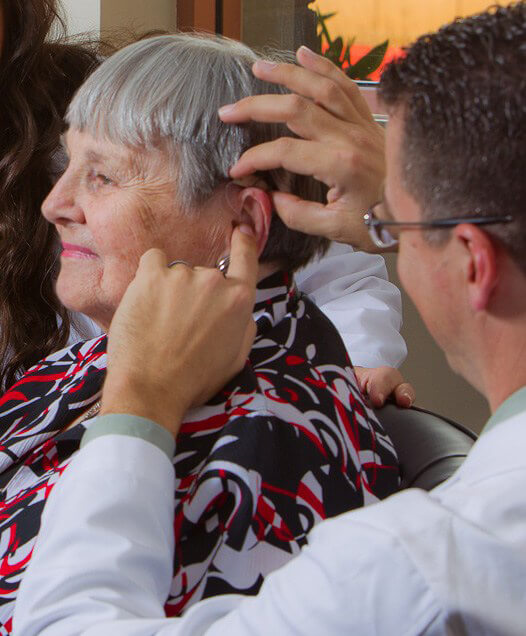 Doctor of Audiology student examining a senior woman's ear