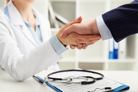 Doctor shaking hands with man in suit