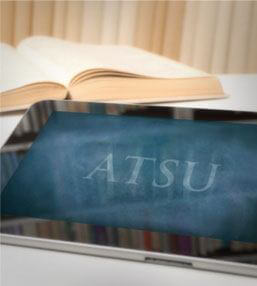 An iPad logging into ATSU's app with an open book displayed in the background