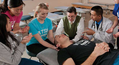 Female osteopathic medical school student practicing low amplitude osteopathic manipulative treatment (OMT) on fellow student under the supervision of a professor to emulate a patient scenario.