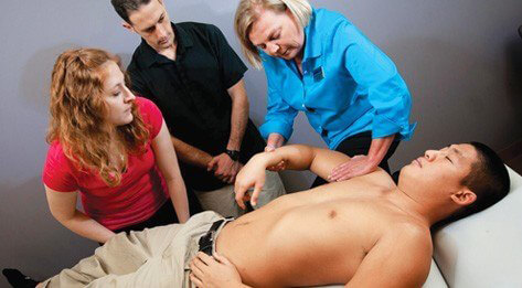 ATSU Physical Therapy students examining a young Asian man lying on a patient table.
