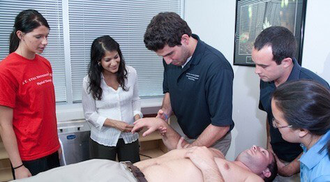 Group of ATSU Physical Therapy students examining a man lying shirtless on a patient table.