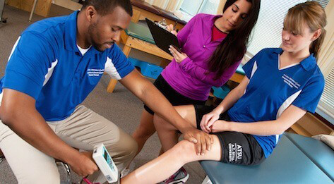 ATSU Physical Therapy students examining the knee of another student.
