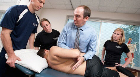 ATSU Physical Therapy students looking on as their instructor examines the back of a young man.
