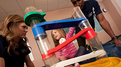 ATSU Physical Therapy students playing with a young girl in a striped pink shirt.