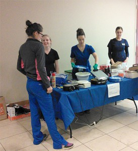 Erin Feller, D2, Tara Brantley, D2, Angela Wilson, D2 and Kristen Linaker, D2, staff the waffle, donut, juice and coffee table in the 5835 building as part of the SUAT breakfast fundraiser.