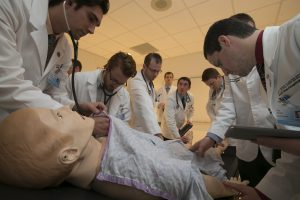 During a physiology lab at ATSU-KCOM, students take turns reading the pulse of a manikin. In addition to reading vital signs, they also simulate intubations, CPR, and IV infusions.