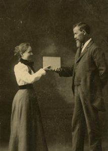 Dr. Still handing book to woman