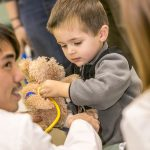 A young boy uses a stethoscope on his teddy bear.