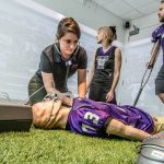 In the simulation room, ATSU-KCOM medical education fellow Brianne Haggard listens to the heartbeat of a manikan, playing the role of a football player suffering from an asthma attack. Fellows Nichole Norgard and Kyle Baum stand nearby to help.