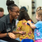 Physical therapy student plays blocks with a child at the annual Baby Lab