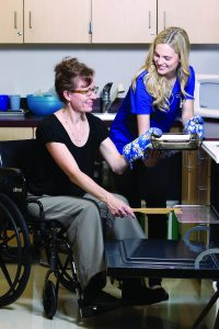 Student helps a woman in a wheelchair to put a casserole dish in the oven.