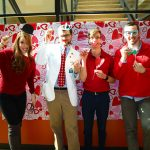 Students dressed in red in with photo booth props