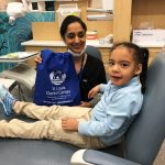 Dentist with young patient holding sports bag