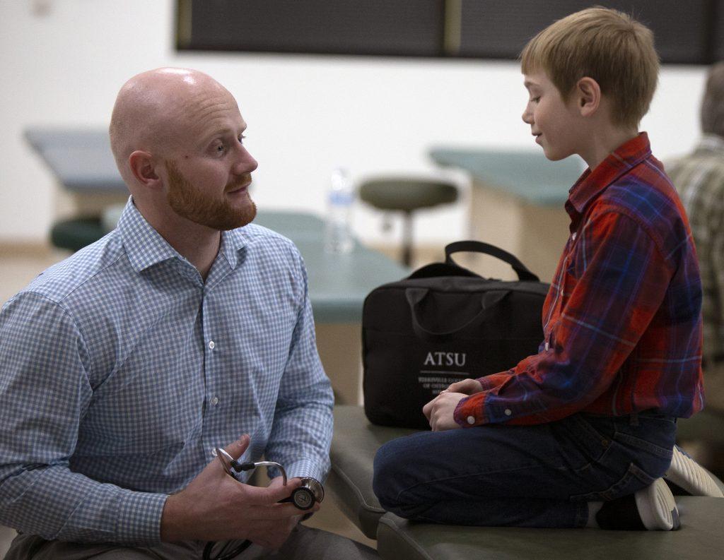 An ATSU-KCOM student works with a child during a pediatrics lab