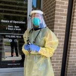 Dr. Linnette Sells in PPE standing outside her clinic