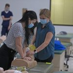 students performing CPR on manikin