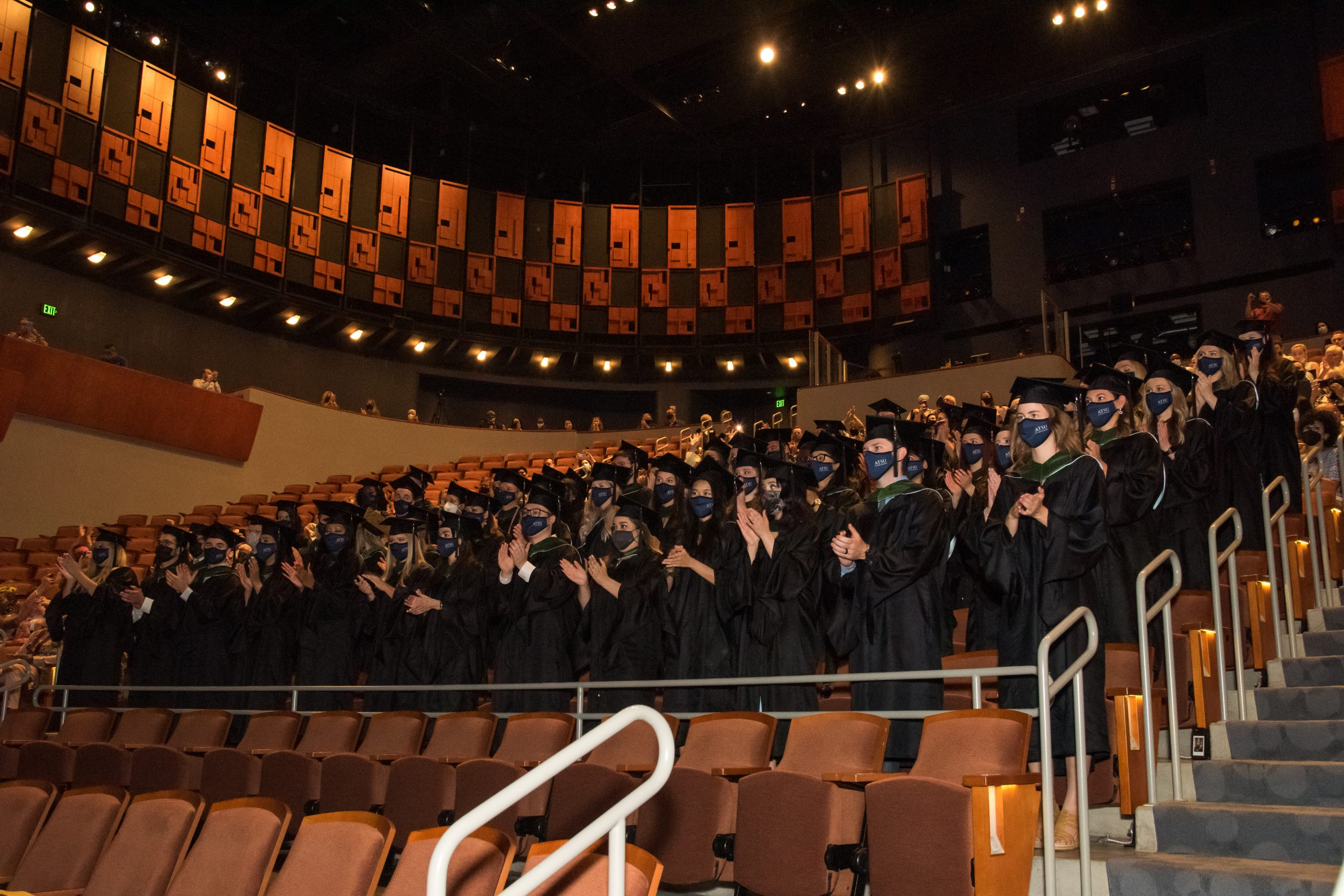 Graduates stand and applaud during the ATSU-ASHS residential Physician Assistant program commencement ceremony.