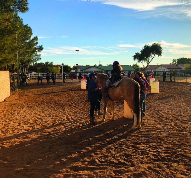 hippotherapy with child on horse and two side walkers at Arizona ranch