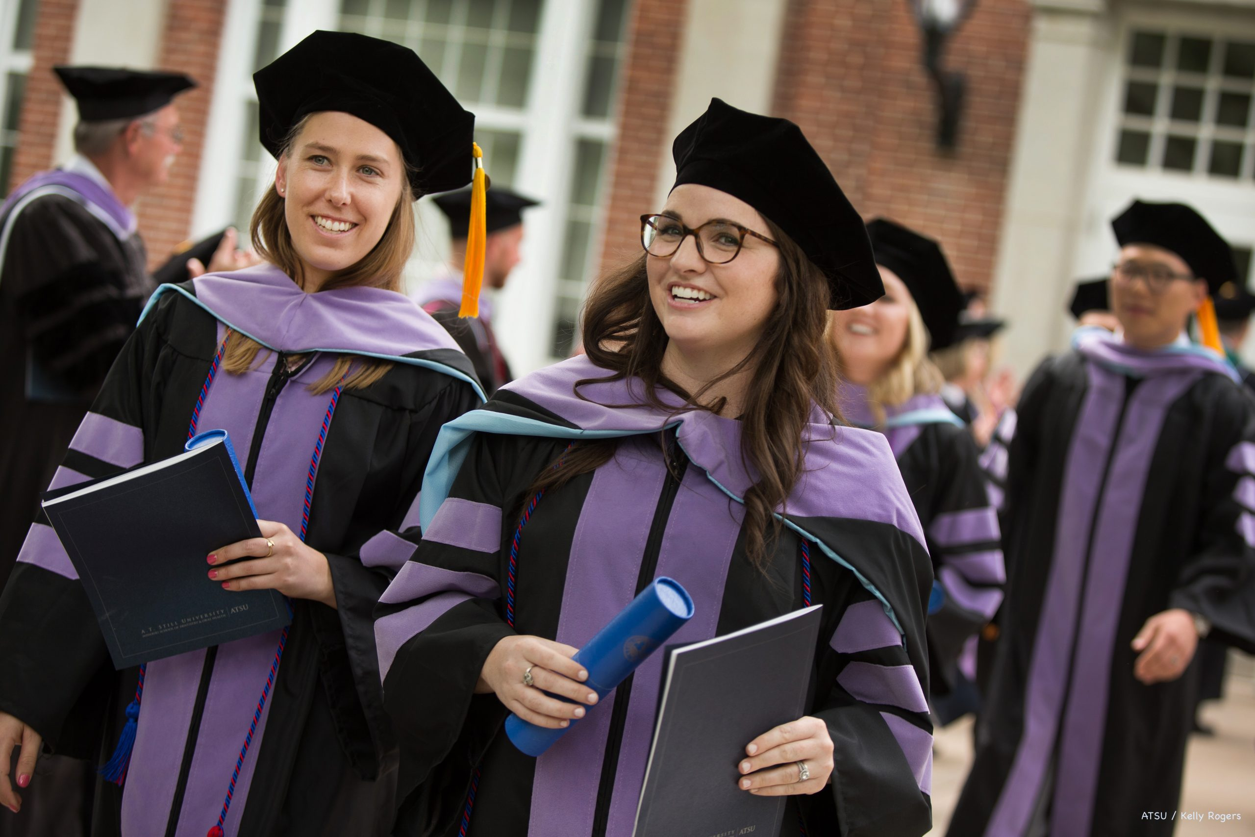 Graduates walk out of Baldwin Hall Auditorium holding their diploma.