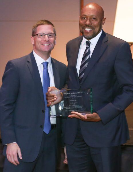 2 men standing with award