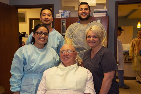 group smiling surrounding veteran with new dentures