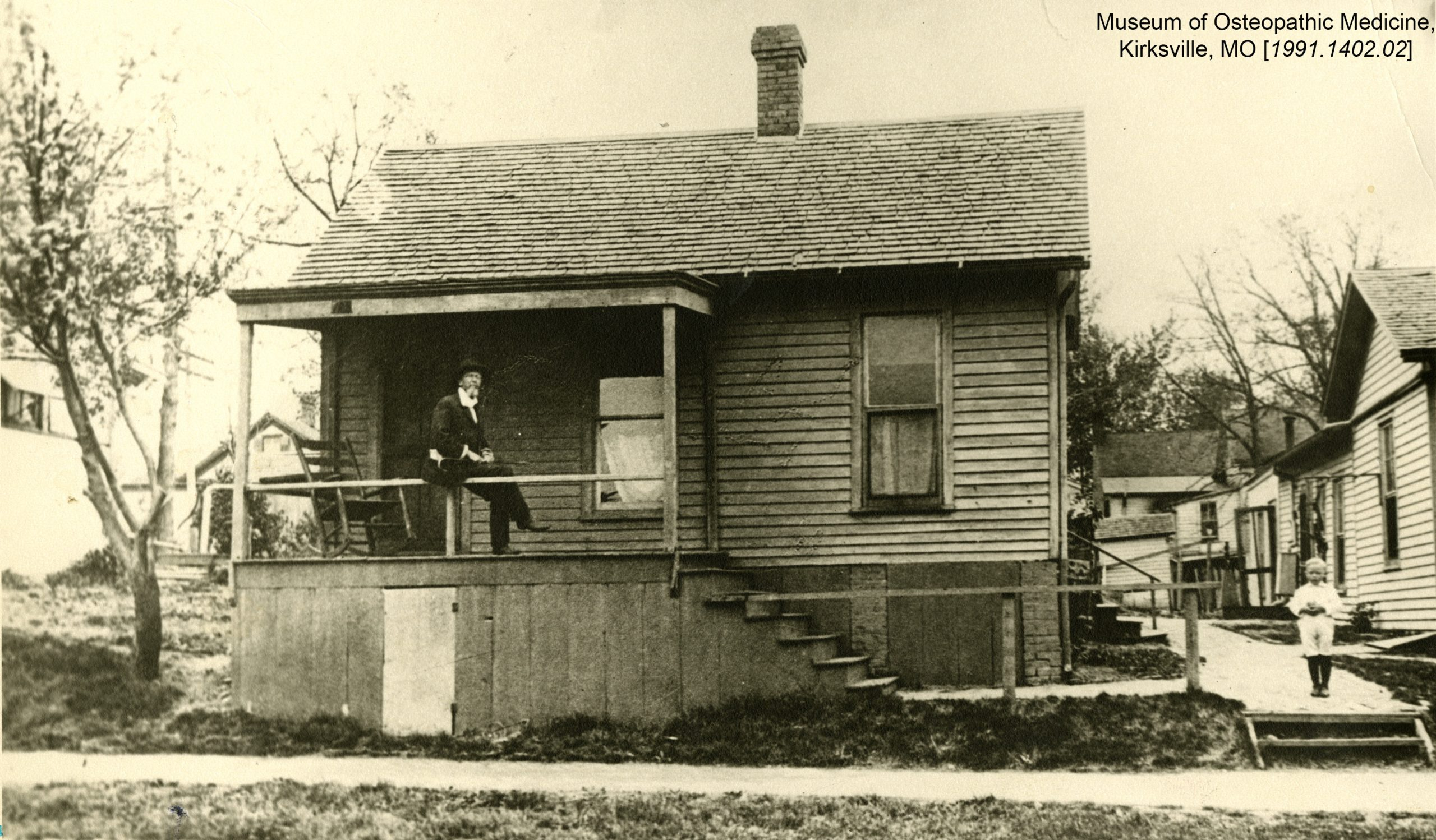Dr. Still sits on the porch of the first school of osteopathic medicine. Museum of Osteopathic Medicine, Kirksville, Missouri [1991.1402.02]