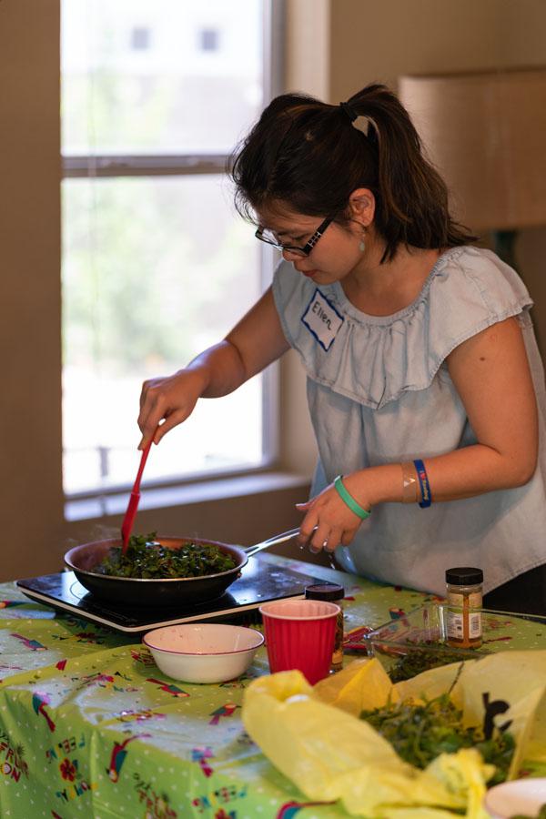 Ellen Tran, OMS II, stirs food in a pan.