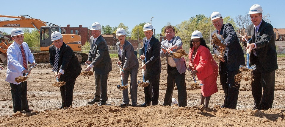 Members of the stage party turn the dirt at the clinic site.