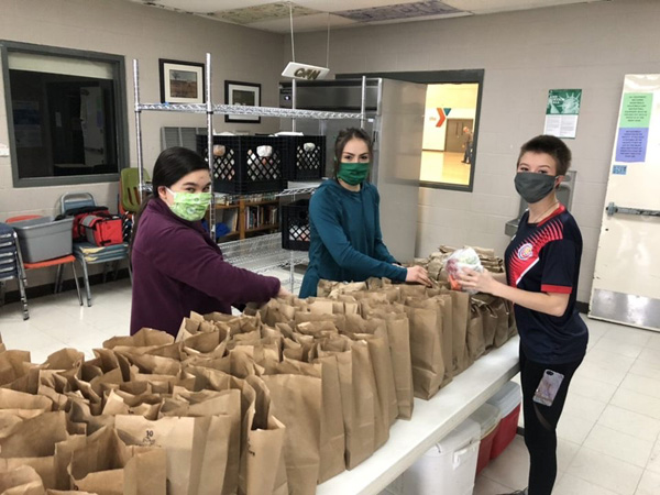 three students putting lunch together in paper bags