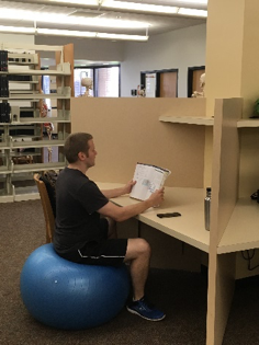 Student using a stabilization ball in the library