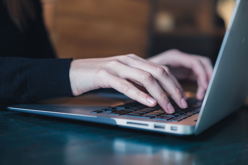Hands sitting on a laptop
