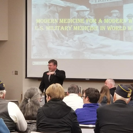 Lecturer speaking at the open house for the WWI exhibit at the Missouri library