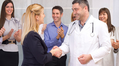 Male doctor in white lab coat shaking hands with a blonde female in a black suit.