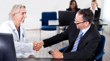 Male doctor in white lab coat shaking hands with a professional male in a black suit.